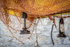 Oil lamps and fishing net. Beautiful decoration of a terrace in a small fishing village Royalty Free Stock Photos