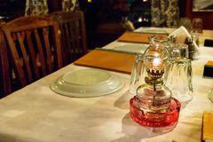 Oil lamps on a table of a greek tavern, selective focus. Oil lamps on a table inside a greek traditional tavern - restaurant in Larissa, Greece Royalty Free Stock Photo