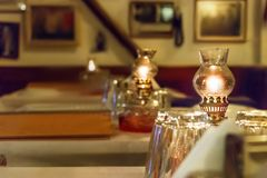 Oil lamps on a table of a greek tavern, selective focus. Oil lamps on a table inside a greek traditional tavern - restaurant in Larissa, Greece Stock Photos