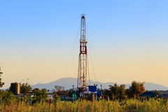 Oil Land Drilling Rig Working In The Field. For Petroleum Exporation at Sunset Time Royalty Free Stock Photography