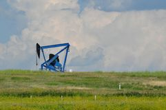 Oil lease against clouds. Oil lease on the prairies Royalty Free Stock Photo