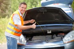 Oil level check. Man checking level of oil on a car engine dipstick, and showing ok sign Royalty Free Stock Photo