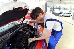 Oil level control of engine oil on the car by a professional mechanic stock images