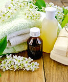 Oil with lotion and bird cherry on board Stock Photo