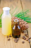 Oil and lotion with cedar cone on board Stock Photo