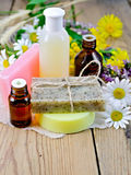 Oil with lotion and soap with wildflowers on the board Stock Photography