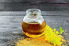 Oil mustard in jar with flower on board royalty free stock image