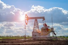 Oil and natural gas production tower in the field with a bright sun glare stock photo