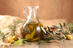Oil olive bottle with branch. On wood background royalty free stock photos