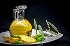 Oil and olive composition. A compisition made by a jar full of oil, an olive branch, some olives and an italian frisella on a black background Royalty Free Stock Image