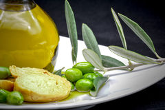 Oil and olive composition. A compisition made by a jar full of oil, an olive branch, some olives and an italian frisella on a black background Stock Photo