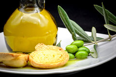 Oil and olive composition. Some olives and a jar full of oil and a branch of olive tree on a white dish on a black background stock photo