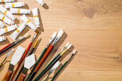 Oil paint and other tools. Top view of wooden desktop with oil paint tubes, brushes and other drawing tools. Mock up royalty free stock photography