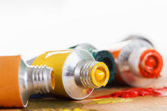 Oil paint tubes and pain brush over colorful artist's palette Royalty Free Stock Image