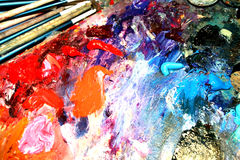 Oil painting palette and brush. Artists oil paints and brush multi coloured close up semi abstract Stock Photography
