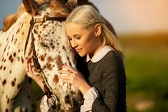 Oil painting in rococo time. Sensual woman embracing horse in sunlight stock photos