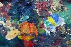 Oil paints and brushes on the old easel and color palette. And tubes of the artist royalty free stock photography