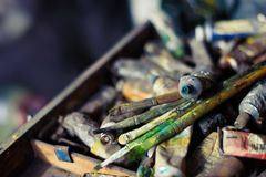 Oil paints and brushes on the old easel and color palette. And tubes of the artist Stock Photo