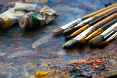 Oil paints and paint brushes on a palette. Oil paints and paint brushes on a palette close up Royalty Free Stock Images