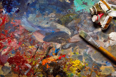Oil paints and paint brushes on a palette. Oil paints and paint brushes on a palette close up Stock Photo