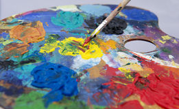 Artists Pallet and Brush. Oil paints on pallet with various colours sitting on old wooden boards royalty free stock photo