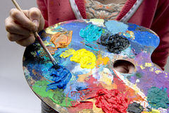 Artists Pallet and Brush. Oil paints on pallet with various colours sitting on old wooden boards stock photography