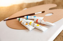 Oil paints in tubes and paintbrush lying on wooden pallet. Colorful oil paints in tubes and paintbrush lying on wooden pallet stock photos