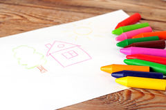 Oil pastel crayons lying on a paper with painted children's draw Royalty Free Stock Photo