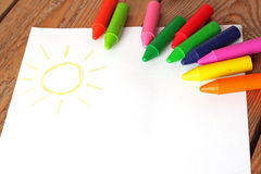 Oil pastel crayons lying on a paper with painted children's draw Royalty Free Stock Photos