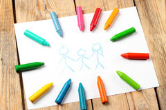 Oil pastel crayons lying on a paper with painted family Royalty Free Stock Image