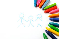 Oil pastel crayons lying on a paper with painted family Royalty Free Stock Photo