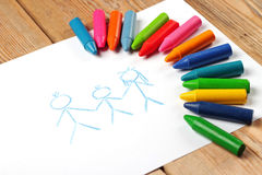 Oil pastel crayons lying on a paper with painted family Stock Photos