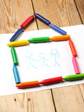 Oil pastel crayons lying on a paper with painted family Royalty Free Stock Images