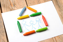 Oil pastel crayons lying on a paper with painted family Royalty Free Stock Photos