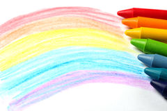 Oil pastel crayons lying on a paper with painted rainbow Stock Image