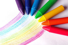 Oil pastel crayons lying on a paper with painted rainbow Royalty Free Stock Photos
