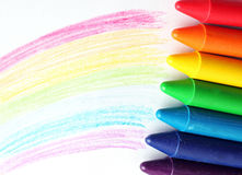 Oil pastel crayons lying on a paper with painted rainbow Stock Photo