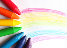 Oil pastel crayons lying on a paper with painted rainbow Royalty Free Stock Photography