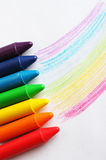 Oil pastel crayons lying on a paper with pictured rainbow Stock Photos