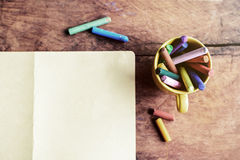 Oil pastels with blank paper on old wooden background Stock Images
