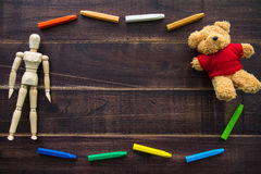 Oil pastels and toys doll on the table brown wood. Stock Images