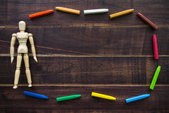 Oil pastels and toys doll on the table brown wood. Royalty Free Stock Photography