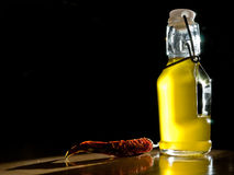 Oil and pepper. A bottle of olive oil, and a chili pepper Stock Photography