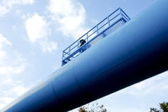 Oil pipeline. Blue thick piping shine in blue sky royalty free stock image