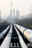 Oil pipeline and oil refinery against light royalty free stock photography
