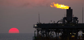 Oil platform and flare at sunset Stock Photo