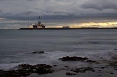 Oil platform and wind turbine at sunset. Playa de Arinaga. Aguimes. Gran Canaria. Canary Islands. Spain royalty free stock photos