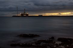 Oil platform and wind turbine at sunset. Playa de Arinaga. Aguimes. Gran Canaria. Canary Islands. Spain royalty free stock images