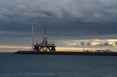 Oil platform and wind turbine at sunset. stock image
