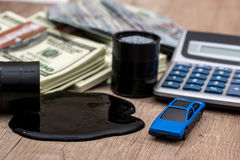 Oil pool and barrels with dollars, calculator and toy car. On the table Royalty Free Stock Images